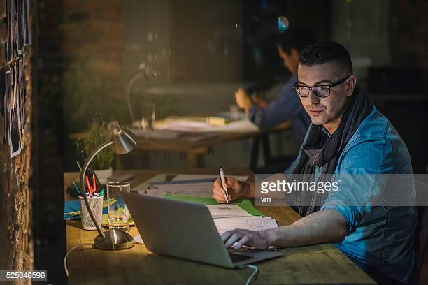Creative professional using laptop and writing notes