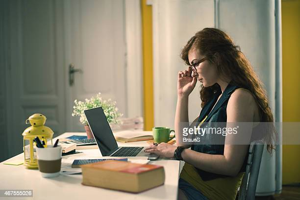 Creative redhead woman using laptop in her study.