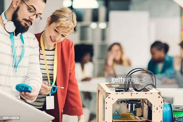 Creative Start-Up Business Team Working by 3D Printer.