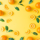 Creative summer pattern made of oranges and green leaves on pastel yellow background. Fruit minimal concept. Flat lay.