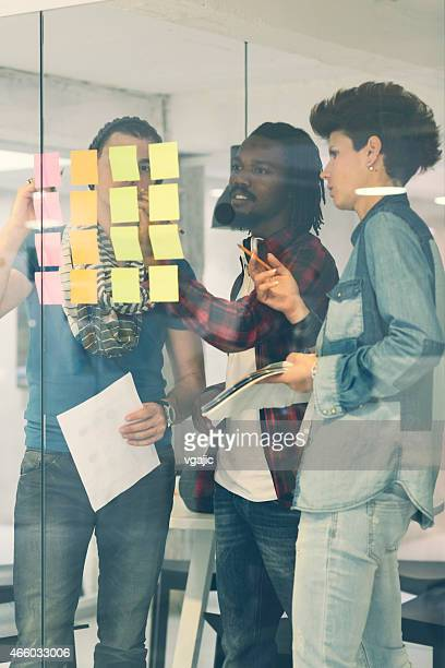 Equipo creativo mirando en notas adhesivas y escrito.