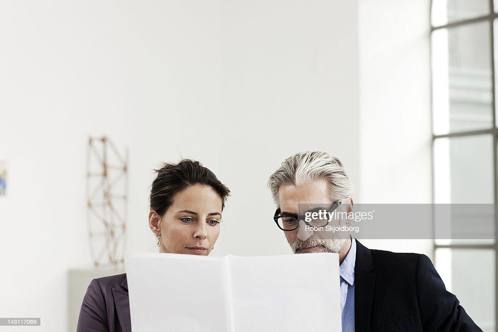Creative woman and mature man looking at sketches : Stock Photo
