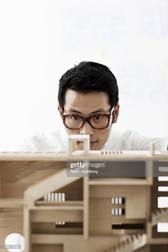 Creative young man looking at scale model of wood : Stock Photo