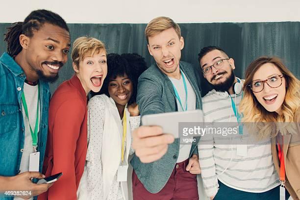 Groupe de jeunes gens créatifs en Selfie.