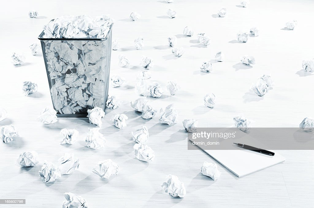 Creativity block? Many crumpled paper balls scattered on white floor