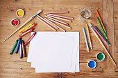 Blank paper with painting supplies and pencils on a wooden table