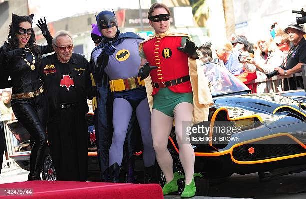 Creator of the Batmobile George Barris poses with characters dressed in costume ahead of a ceremony for Adam West who played Batman in the original...