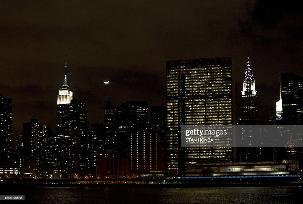 A crecent moon sets over the Manhattan skyline in this view of the Empire State Building (L), the United Nations headquarters (C) and the Chrysler Building (R) February 25, 2012 in New York. AFP PHOTO/Stan HONDA
