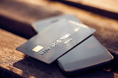 Credit card and mobile phone on a wooden background. Concept for mobile payments.