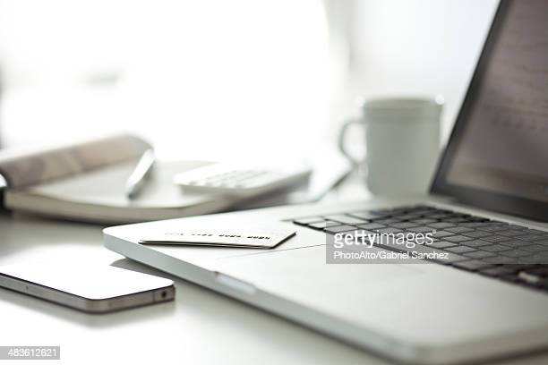Credit card resting on laptop computer in home office