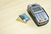 Credit card with payment terminal on wooden desk