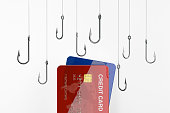 Two credit cards and many fishing hooks. Credit card security and phishing concept. One of the credit cards is red and the other one is blue. There are several fishing hooks above credit cards. Isolat