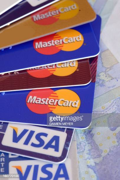 Credit cards are pictured near 20 euros banknotes on February 5 2013 in Rennes western France French police has arrested early this morning in Paris...
