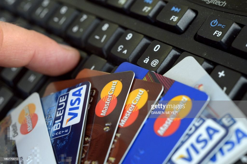Credit cards are pictured on a computer's keyboard on February 5, 2013 in Rennes, western France. French police has arrested, early this morning in Paris and in several French and overseas departments, 22 people in connection with the trade of credit cards numbers on internet.