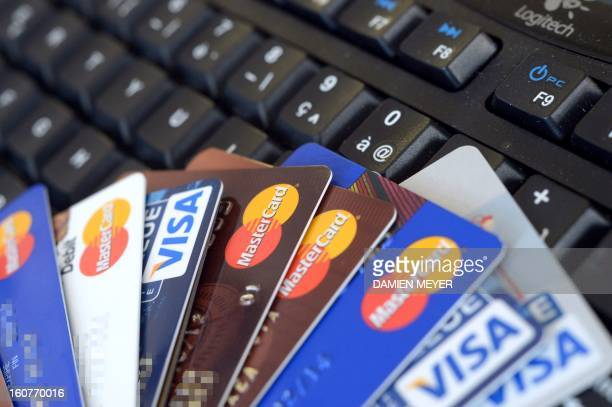 Credit cards are pictured on a computer's keyboard on February 5 2013 in Rennes western France French police has arrested early this morning in Paris...