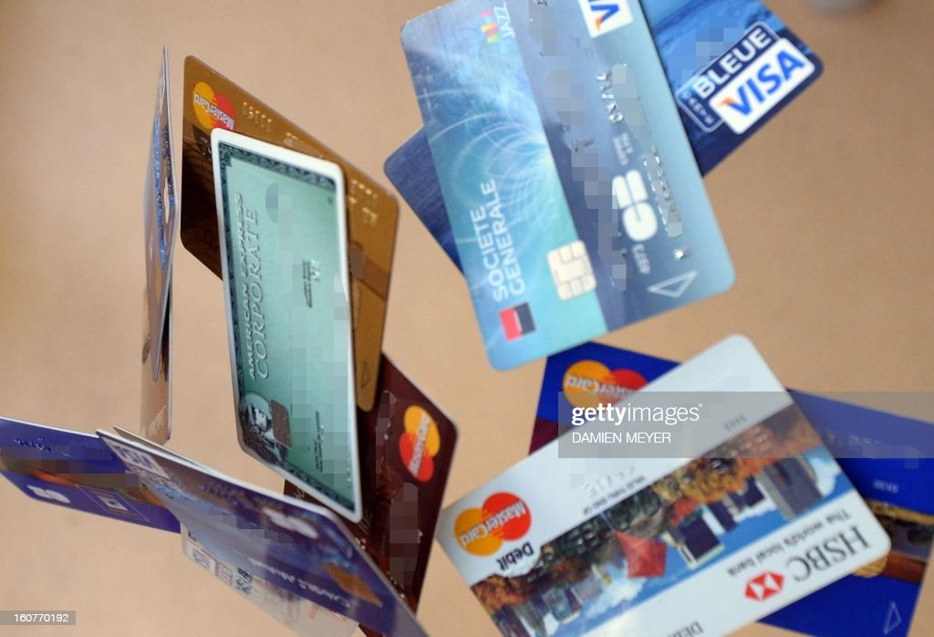 Credit cards falling down are pictured, on February 5, 2013 in Rennes, western France. French police has arrested, early this morning in Paris and in several French and overseas departments, 22 people in connection with the trade of credit cards numbers on internet. AFP PHOTO DAMIEN MEYER