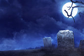 Creepy atmosphere in the cemetery in the night , by moonlight, mist and trees that live twigs. Halloween background concept