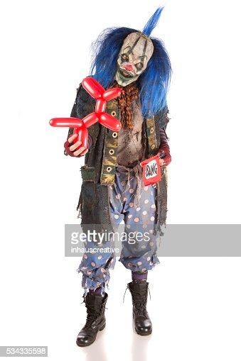 Creepy Clown holding a ballon animal and pop gun