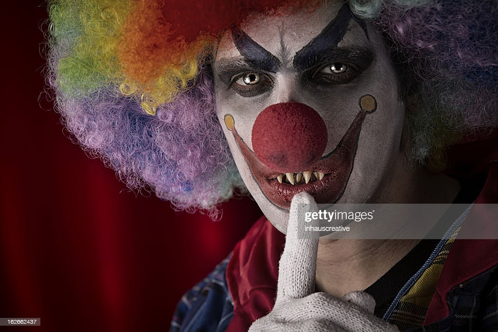 Creepy Clown with fingers on lips. This stock image has a horizontal composition.
