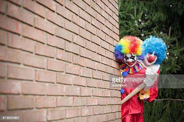 Creepy Clowns Peeking Around A Brick Wall
