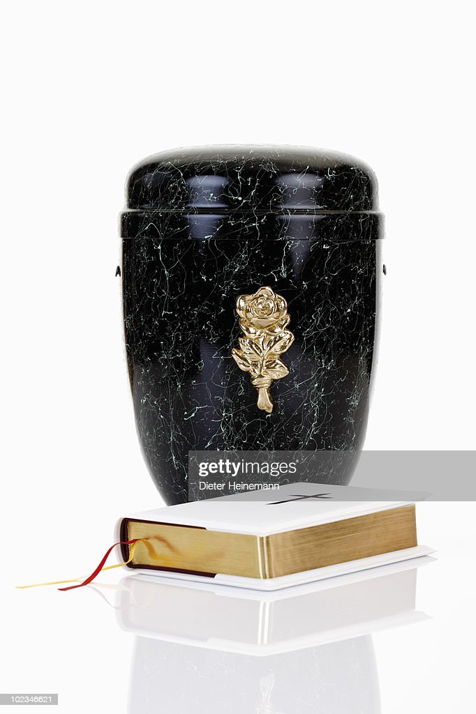 Cremation urn and bible against white background