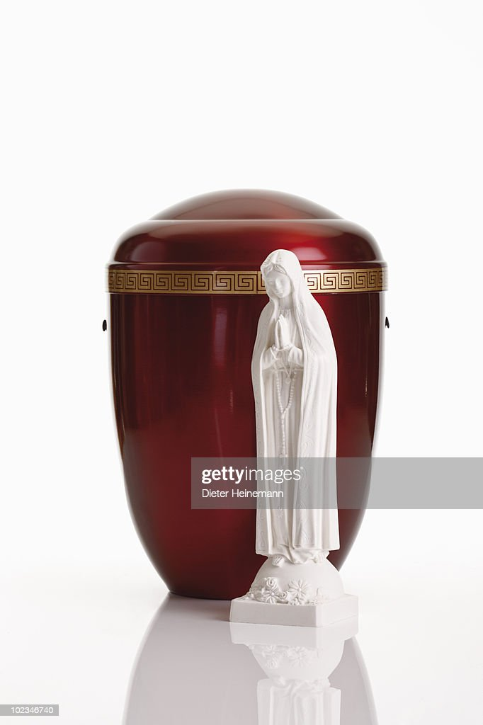 Cremation urn and statue of Virgin Mary against white background