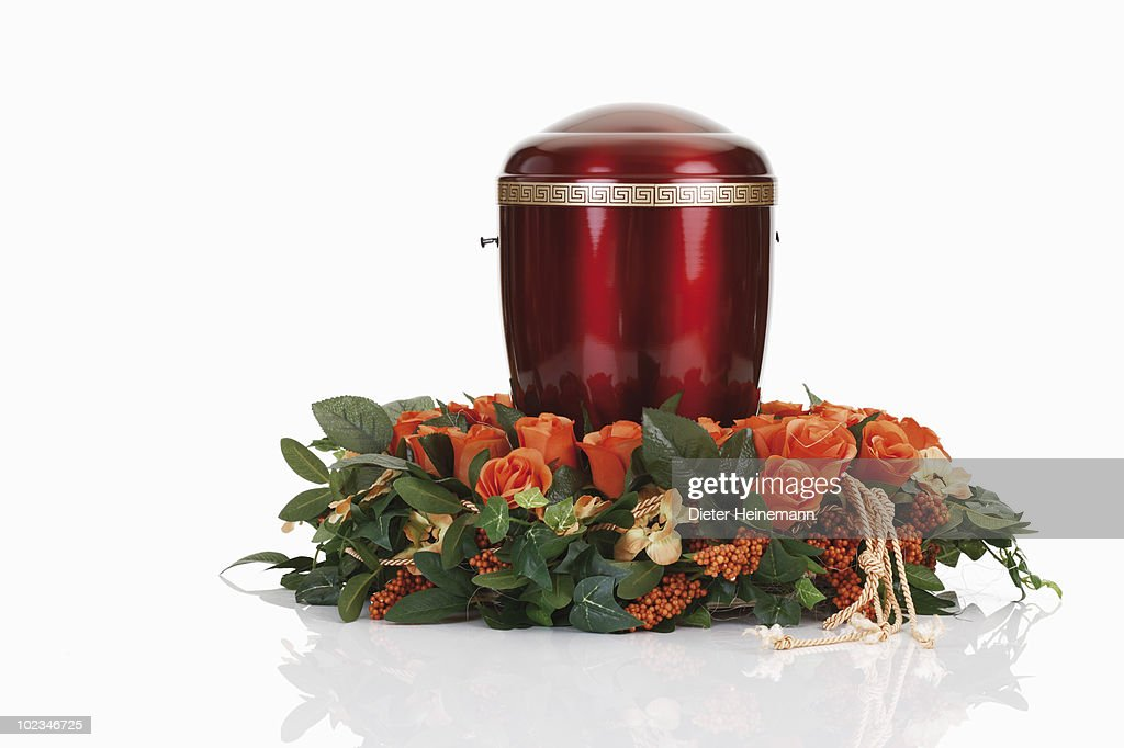 Cremation urn with wreath against white background