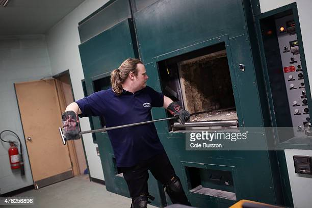 Crematorium technician Jonathan Prideaux scrapes ashes and bones from a cremation oven at St John's Norway Cemetery and Crematorium on June 17 2015...