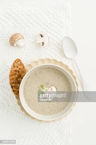 Creme of mushroom soup in white soup bowl, baguette slice