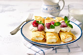 Crepes stuffed with ricotta on a vintage plate on a light slate,stone or concrete background.