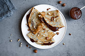 Crepes with chocolate spread and hazelnuts. Homemade thin crepes for breakfast or dessert.