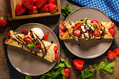 Crepes with ice cream, caramel topping and strawberries. Delicious homemade caramel creame