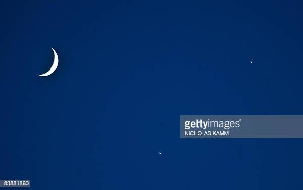 A crescent moon and the planets Venus and Jupiter are seen in a rare alignment over Washington on December 1 2008 AFP PHOTO/Nicholas KAMM