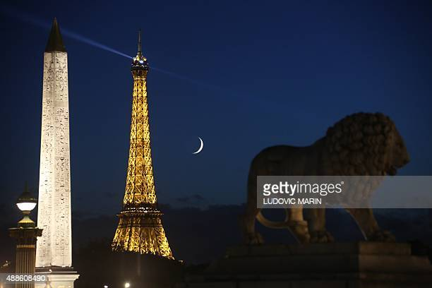 A crescent moon is pictured floating between the sculpture of a Lion the Eiffel Tower and the the Egyptian Obelisque of Place de la Concorde on...