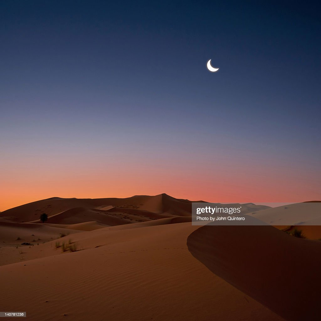 Crescent moon over dunes