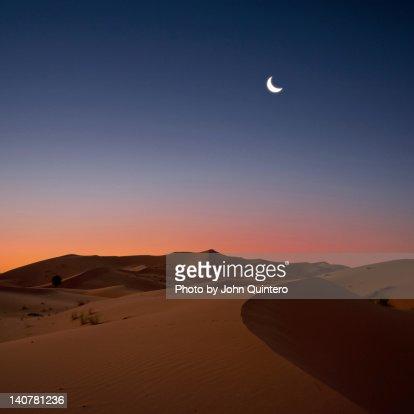 Crescent moon over dunes