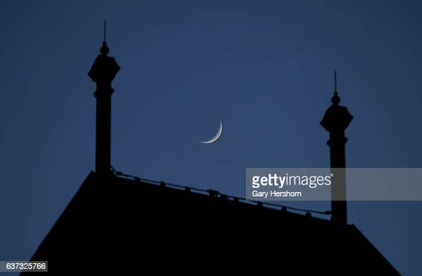 A crescent moon sets behind a building in Liberty State Park on January 1 2017 in Jersey City NJ