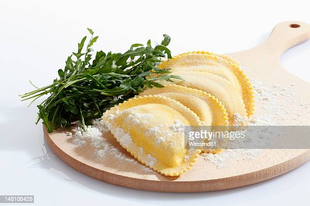 Crescent shape pasta with flour and rocket on chopping board