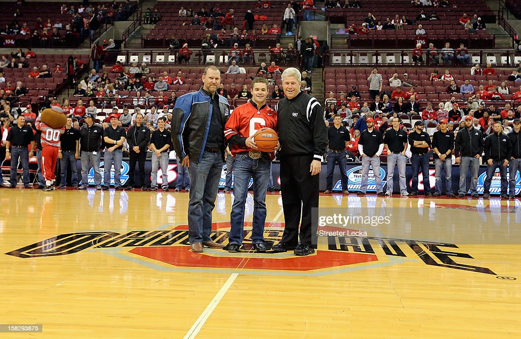 Crew chief Mike Kelley takes a picture of NASCAR Nationwide Series Champion Ricky Stenhouse Jr. as he gives out the game ball at an Ohio State Basketball game during the NASCAR Nationwide Series Champion's Day on December 12, 2012 in Columbus, Ohio