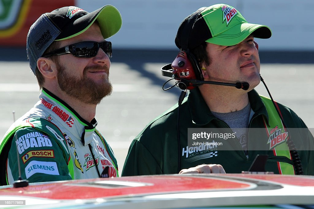 Crew chief Steve Letarte talks to Dale Earnhardt Jr., driver of the #88 Diet Mountain Dew Chevrolet, on the grid during qualifying for the NASCAR Sprint Cup Series STP Gas Booster 500 on April 5, 2013 at Martinsville Speedway in Ridgeway, Virginia.