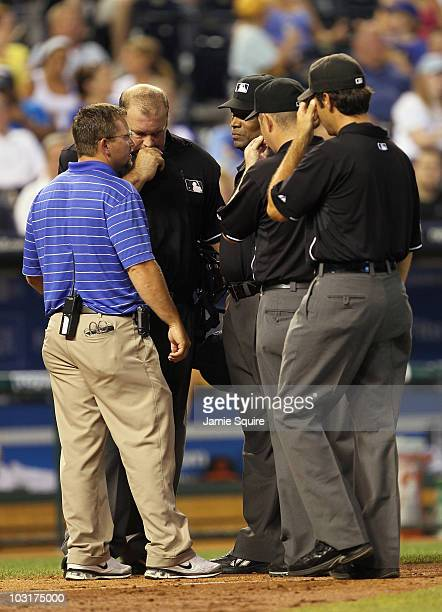 Crew chief Wally Bell talks with other umpires and trainer prior to leaving the game during the 6th inning between the Baltimore Orioles and the...