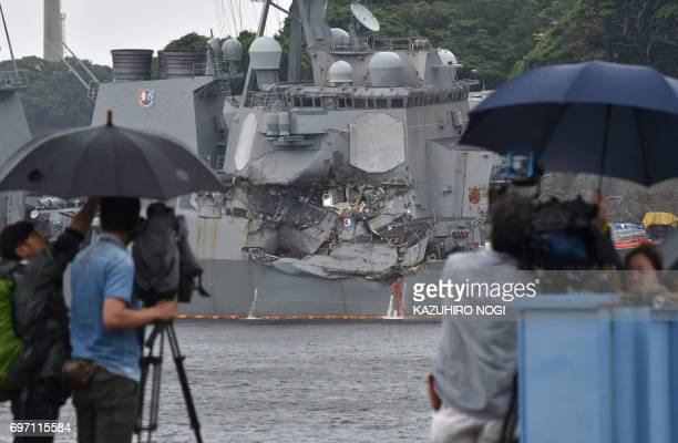 A TV crew films the damages on the guided missile destroyer USS Fitzgerald at its mother port in Yokosuka southwest of Tokyo on June 18 2017 A number...