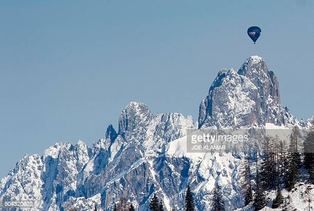 A crew flies their hot air balloon near the Tyrollean peak of Bischofsmuetze 2458 meter high seen from the course of the women's SuperG of FIS Ski...