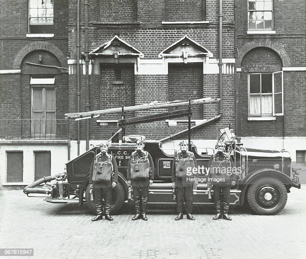 Crew in breathing apparatus London Fire Brigade Headquarters London 1934 Fire engine with ladder and fire hose visable Uniformed firemen posing...