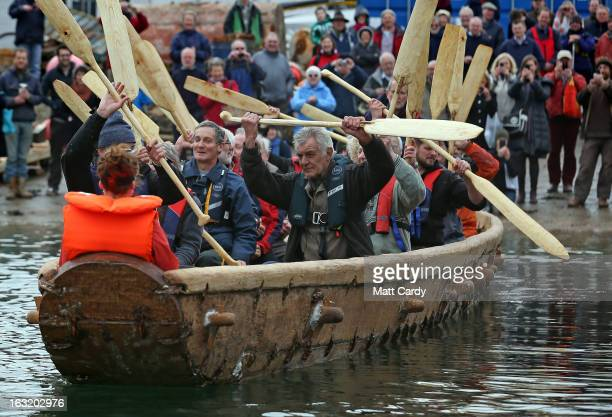 Crew in Britain's first ever fullsize reconstructed seagoing Bronze Age boat raise their paddles out as it makes its maiden voyage on March 6 2013 in...