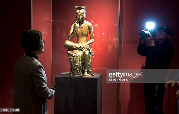 TV crew in the Metropolitan Museum of Art talks about the Bodhisattva in a pensive pose which is part of the Silla Exhibit October 28 2013 at the...