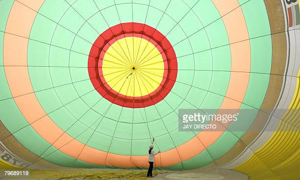 Crew inflate colorful hot air balloons at the former US air base of Clark north of Manila during the 12th hot air balloon show on February 10 2008...
