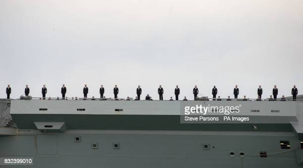 Crew line the deck of HMS Queen Elizabeth as the UK's newest aircraft carrier arrives in Portsmouth for the first time