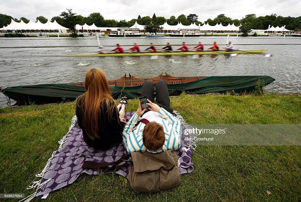 A crew makes its way to the start as a couple relax on the riverbank during the Henley Royal Regatta on June 29, 2016 in Henley-on-Thames, England.