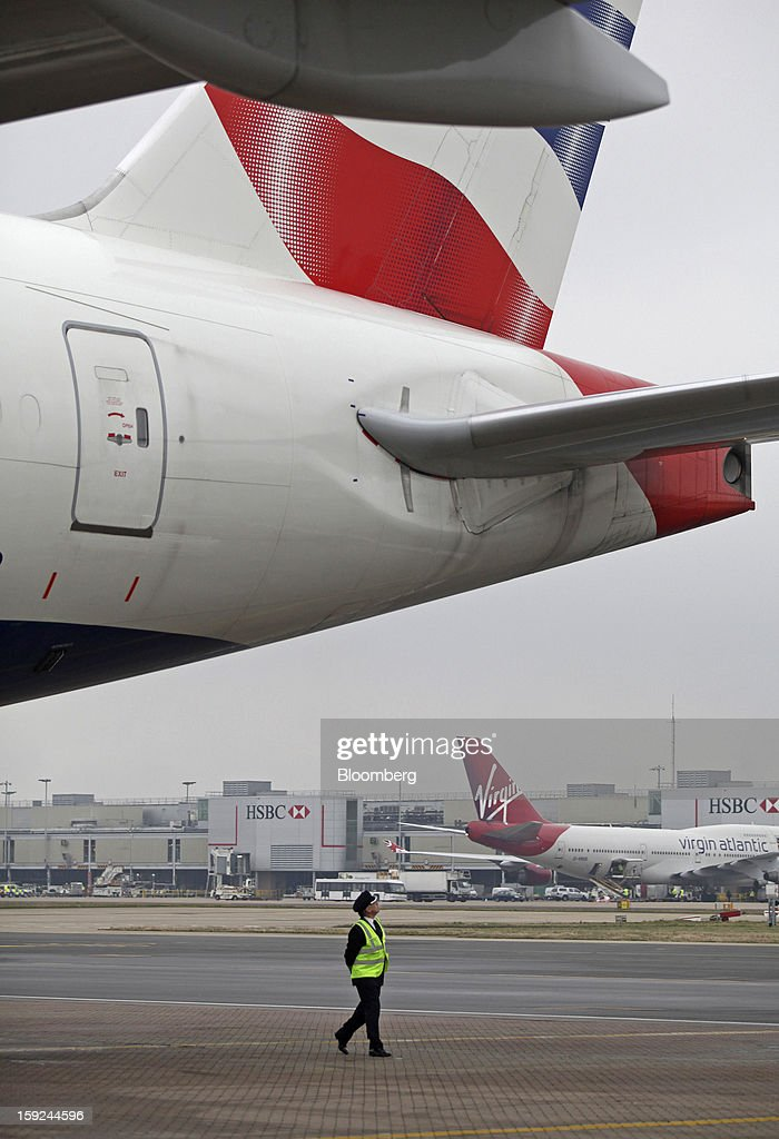 A crew member checks the rear of a British Airways aircraft at Gatwick airport in Crawley, U.K., on Wednesday, Jan. 9, 2013. Gatwick, acquired by Global Infrastructure Partners Ltd. in 2009 after regulators sought a breakup of BAA Ltd., owner of the larger Heathrow hub, is 30 miles (48 kilometers) south of London and serves about 200 destinations, more than any other U.K. airport, according to flight schedule data provider OAG. Photographer: Chris Ratcliffe/Bloomberg via Getty Images